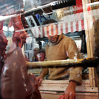 A butcher looks through a the glass of his shop in Izmir, Turkey.