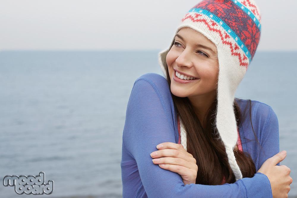 Young woman wearing wool hat on beach portrait