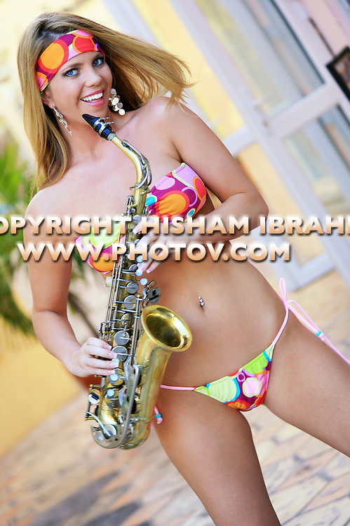 Sexy Blonde woman in bikini playing saxophone, Nassau, Bahamas