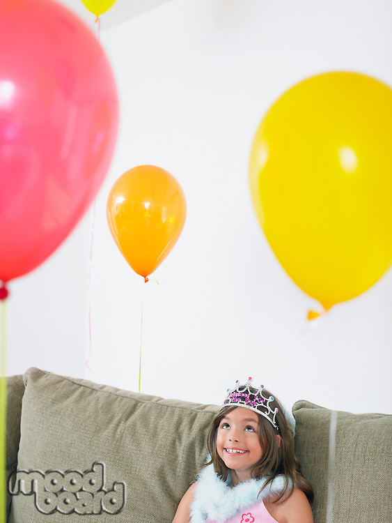 Young girl (7-9) sitting on sofa looking at balloons