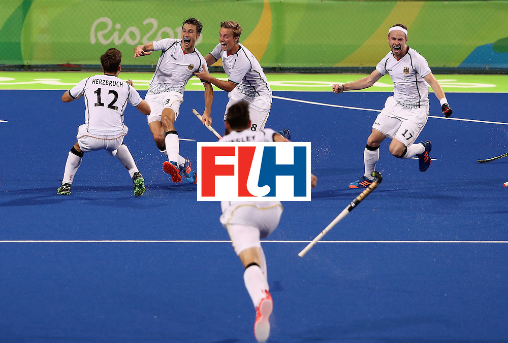 RIO DE JANEIRO, BRAZIL - AUGUST 14:  Florian Fuchs (C) of Germany is mobbed by team mates  after scoring the match winning last second goal during the Men's hockey quarter final match between the Germany and New Zealand on Day 9 of the Rio 2016 Olympic Games at the Olympic Hockey Centre on August 14, 2016 in Rio de Janeiro, Brazil.  (Photo by David Rogers/Getty Images)