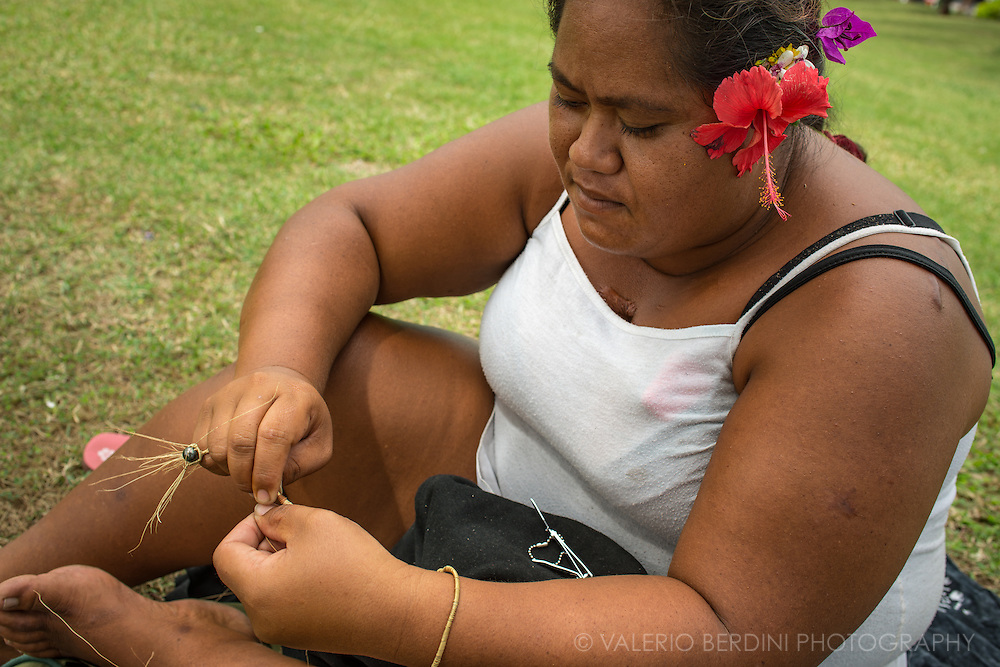 A woman makes a bracelet with a black pearl and coconut fiber sitting in a lawn of a park in Papeete. Tahitian pearls are a key part of Polynesian culture and economy as well as decorating the hair with fresh flowers posed over the ears.