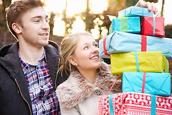 Young Couple Holding Stack of Christmas Presents Outdoors