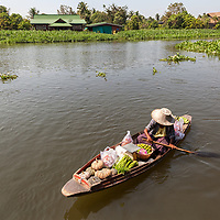 A woman rowing her boat on Tha Chin River in Samphran.