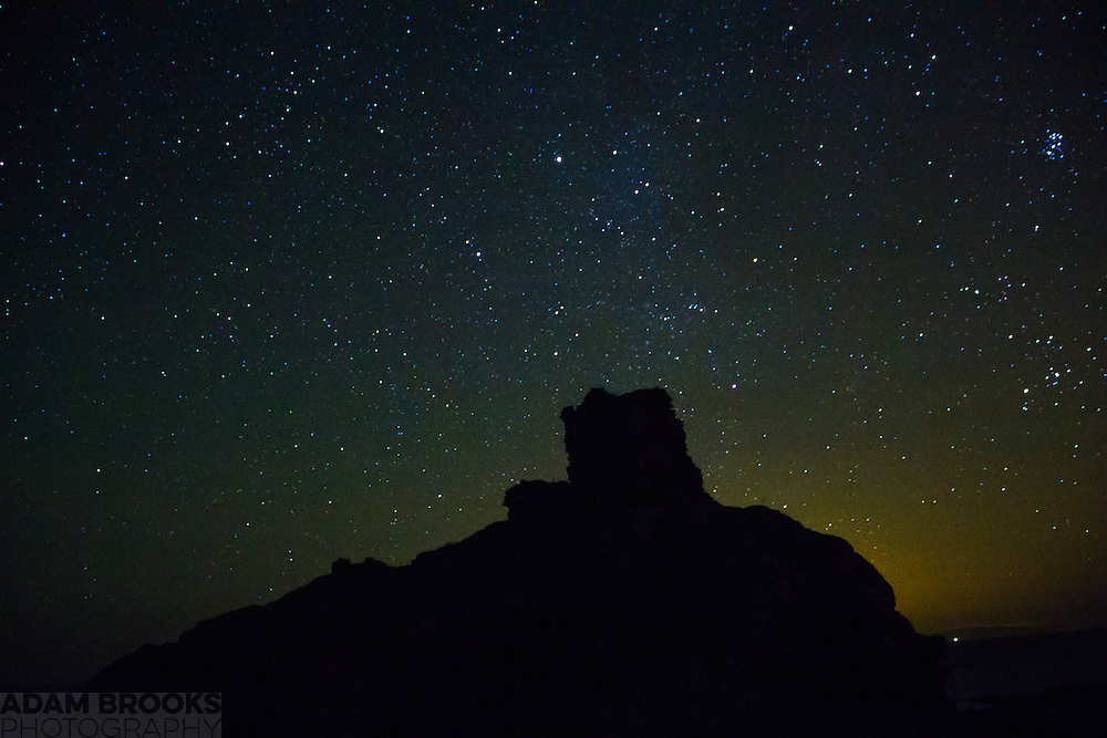 The night sky including The Pleiades off to the top right, with Kinbane Castle in the foreground.
