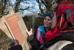 Harefield, UK. 7 February, 2020. Sarah Green and environmental activists from Extinction Rebellion view an old version of a High Court injunction found at the roadside where HS2 engineers have fenced in fellow activists who have climbed a veteran oak tree in order to try to protect it from felling.