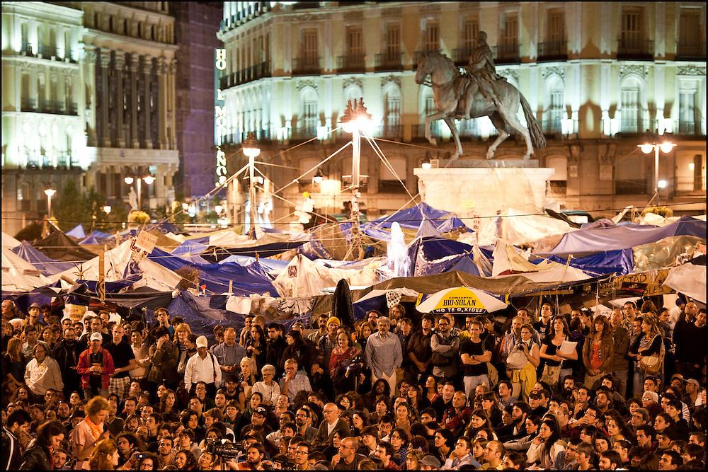 """Chaque soir l'assemblee populaire a lieu de 20h à minuit et permet de s'exprimer sur la place; des propositions sont egalement votees a mains levees. // Le mouvement spontane du """"15 M"""" (15 mai) compose de citoyens espagnols campe depuis 2 semaines sur la place Puerta Del Sol avec pour revendication la construction d'une democratie nouvelle. Organise en commission les citoyens prennent la parole lors d'assemblee ouverte a tous - Place Puerta Del Sol à Madrid le Juin 2011. ©Benjamin Girette/IP3Press"""