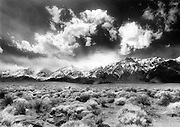 An early spring storm  from the west pushes against the snow-capped Eastern Sierras as seen from Highway 395 near Lone Pine, California.