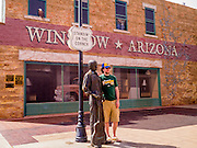 "15 JULY 2012 - WINSLOW, AZ: Tourists with the statue of Jackson Browne in the Standin' on the Corner park at the intersection of Kinsley Avenue and Second Street in Winslow, AZ. The park is based on the Eagles song, written by Jackson Browne and Glenn Frey, the second verse is ""Well, I'm a standing on a corner, In Winslow, Arizona, And such a fine sight to see. It's a girl, my lord .In a flatbed Ford, Slowin' down to take a look at me"" The park has a statue of Jackson Browne and flatbed Ford parked nearby. There is also a mural of the scene on a wall behind the statue.       PHOTO BY JACK KURTZ"