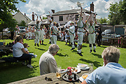 Thaxted Morris Weekend 3-4 June 2017<br /> A meeting of member clubs of the Morris Ring celebrating the 90th anniversary of the founding of the Thaxted Morris Dancing side or team in Thaxted, North West Essex, England UK. <br /> Cambridge side dancing and drinking beer at The Horse and Groom pub at Cornish Hall End, Essex.<br /> Hundred of Morris dancers from the UK and this year the Silkeborg side from Denmark spend most of Saturday dance outside pubs in nearby villages where much beer is consumed. In the late afternoon all the sides congregate in Thaxted where massed dancing is perfomed along Town Street. As darkness falls across Thaxted the spell binding Abbots Bromley Horn Dance is performed to the sound of a solo violin in the dark.