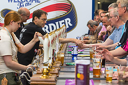 Olympia, London, August 9th 2015. Hundreds of real ale lovers attend the Campaign for Real Ale  Great British Beer Festival at London's Olympia Exhibition Centre, where dozens of independent breweries demonstrate the diversity of British brewed beers. PICTURED: Visitors queue at the beer pumps.