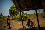 A Xerente indigenous runner trains as his wife sews some artcraft at his village near Tocantinia Brazil, Friday, October 2, 2015.  One nearly empty vastness some decades ago, the northern part of Goias state territory, Tocantins was the latest Brazilian state to be created,  27 years ago. Now, luring Brazilians with an abundance of natural resources, its indigenous heritage, an aura of sustainability, infrastructure and lower prices, the government vows that this solid investment package will make up the facade of a land of opportunity. And eventually attract qualified workforce to populate the area. Profiting from side publicity of two world events, Brazil aims at throwing some light on its developmental potential, and has already helped to transform the locally known national indigenous games in the first international event of this type. In some weeks thousands of indigenous athletes from 24 countries will flock to the arena to compete, share and showcase their faces to the world.  (Hilaea Media/ Dado Galdieri for the Wall Street Journal)