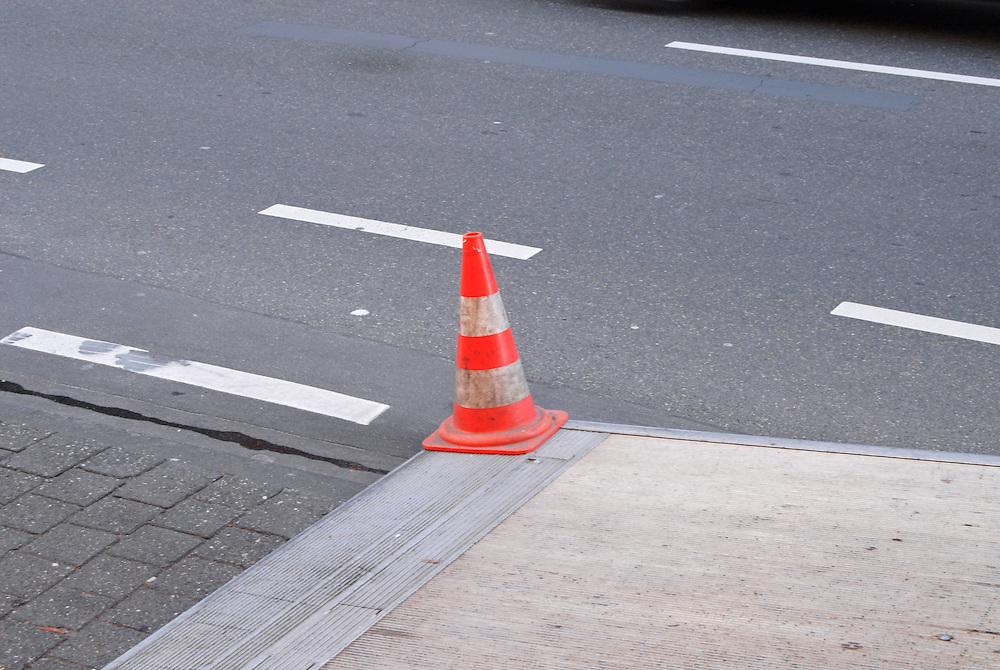 """Ein Warnhut Pylon steht auf der Laderampe eines LKWs am Strassenrand . Die """"Lübecker Hütchen"""" genannten wurden 1952 von Ewald Kongsbak erfunden.            in 1952 Ewald Kongsbak from Luebeck Germany invented the rubber hats as a hint for dangerous situations in traffic. They are called """"Luebecker Huetchen"""". Little Luebeck Hats.  Here stands one on a loading ramp of a lorry """