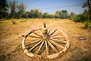 06 APRIL 2013 - SANPATONG, CHIANG MAI, THAILAND:   An old cart wheel in a pasture behind the livestock market in Sanpatong, Chaing Mai province, Thailand. The buffalo market in Sanpatong (also spelled San Patong) started as a weekly gathering of farmers and traders buying and selling water buffalo, the iconic beast of burden in Southeast Asia, more than 60 years ago and has grown into one of the largest weekend markets in northern Thailand. Buffalo and cattle are still a main focus of the market, but traders also buy and sell fighting cocks, food, clothes, home brew and patent medicines.      PHOTO BY JACK KURTZ