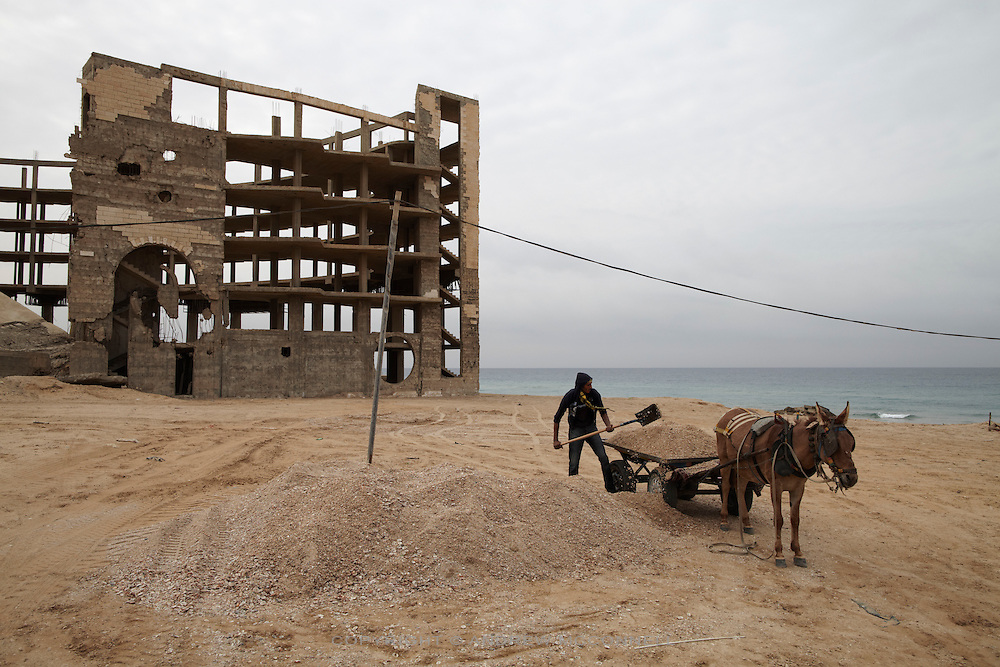 A man shovels shells onto a cart beside the former al-Waha Resort near the northern border with Israel. Shells fetch 50 Shekels (approx EUR10) per tonne and are used to make concrete...