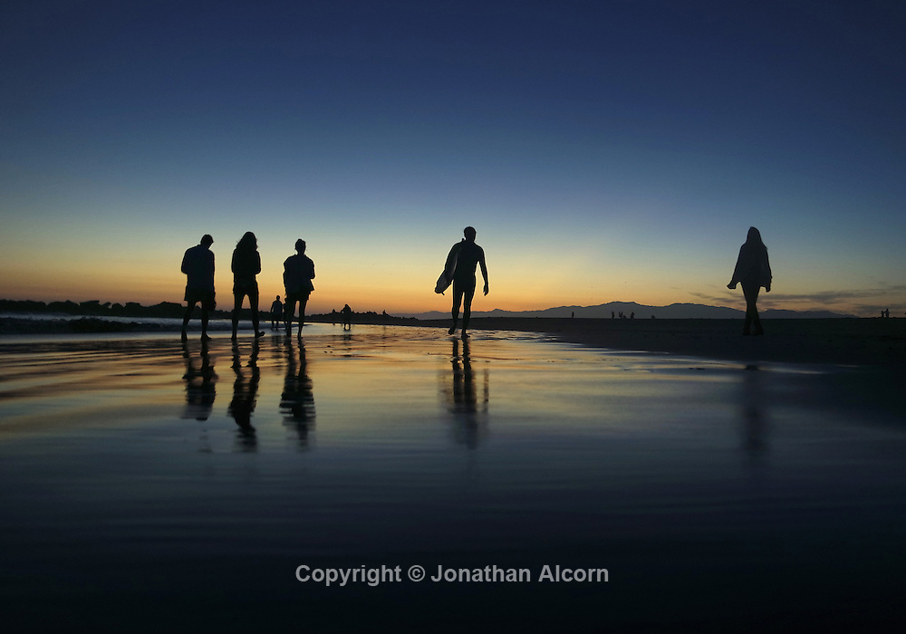 People walk on the Venice Beach shoreline at dusk on the start of Labor Day weekend.