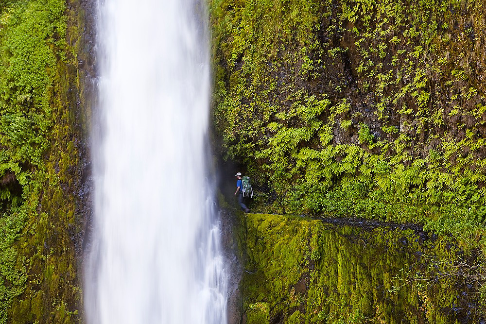 Hiker Zach Podell-Eberhardt walks past Tunnel Falls on the Eagle Creek Trail, cut into the basalt cliff behind the waterfall, in Columbia River Gorge National Scenic Area, Oregon.