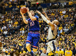 Jan 15, 2018; Morgantown, WV, USA; Kansas Jayhawks guard Sviatoslav Mykhailiuk (10) shoots while defended by West Virginia Mountaineers guard Jevon Carter (2) during the first half at WVU Coliseum. Mandatory Credit: Ben Queen-USA TODAY Sports