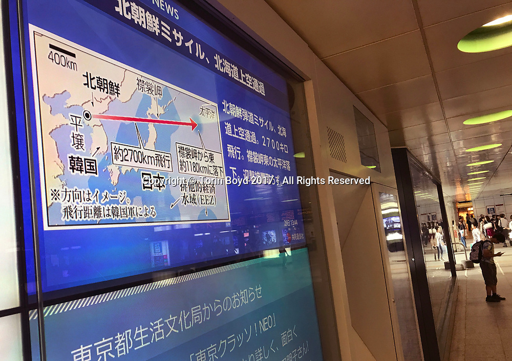 """August 29, 2017, Tokyo, Japan: In the early dawn hours, the people of Japan awoke to learn that North Korea had just fired a missile over it's territory. According to the Japanese government, at 5:58 a.m the intermediate-range missile traveled about 14 minutes and passed over southern Hokkaido for two minutes before plunging into the Pacific Ocean about 1,180 km east of Cape Erimo. When this occurred morning commuters in Hokkaido had their rail service temporally halted due to safety precautions and millions around the country were alerted by emergency notices on their smart phones. In most major cities it was common to see outdoor TV screens broadcasting news throughout the day as seen here in Tokyo. Reacting to the incident, Prime Minister Shinzo Abe called this """"an unprecedented, grave and serious threat"""" that damages the peace and security of the region, adding that Tokyo had lodged a firm protest with Pyongyang. Photo by Torin Boyd."""