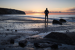 © Licensed to London News Pictures. 23/09/2016. Sandown, Isle of Wight, UK.  A man watching the sunrise at Yaverland beach on the Isle of Wight this morning, 23rd September 2016. The day has started cool, but fine and sunny. It will become a little cloudier and breezier later in the South East of England. Photo credit: Rob Arnold/LNP