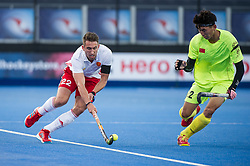 England's David Condon is watched by Talake Du of China. England v China - Hockey World League Semi Final, Lee Valley Hockey and Tennis Centre, London, United Kingdom on 15 June 2017. Photo: Simon Parker
