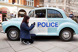 © licensed to London News Pictures. London, UK 26/02/2014. People taking pictures of veteran police cars outside New Scotland Yard as the Met's iconic cop cars dating back to 1948 taking part at a convoy through central London. Vehicles including the 1948 Wolseley, 1970 Morris, Minor 1000 and the 1973 Special Branch Rover P6 leaving Hampton Traffic Garage for the final time to head up to the Met's Peel Centre in Hendon which will be the new home of the fleet. Photo credit: Tolga Akmen/LNP