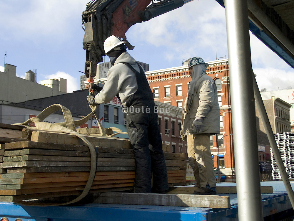 construction workers preparing wood for hoisting