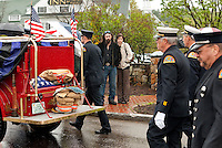 """Members of the Meredith Fire Department march behind the antique Model A with """"Chuck's"""" gear during the procession from Hesky Park following the memorial service for retired Chief Charles """"Chuck"""" Palm Sunday afternoon.  (Karen Bobotas/for the Laconia Daily Sun)"""