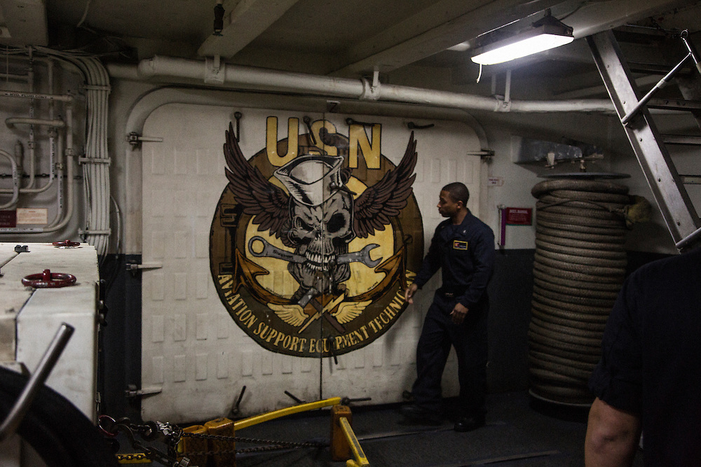 A crew member with the logo of a repair unit on the hanger deck<br /> <br /> Aboard the USS Harry S. Truman operating in the Persian Gulf. February 25, 2016.<br /> <br /> Matt Lutton / Boreal Collective for Mashable
