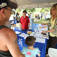 Catherine Smith, an immunization specialist with the Family Resource Center, goes over immunization information with George Derrick, of Guntown, as he and his family attend the Child Safety Day at the Family Resource Center in Tupelo Monday afternoon.