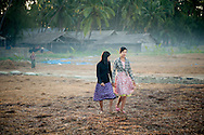 Myanmar, Ngapali. Two young girls go for a walk in the morning.<br /> Every single morning all the fisherman from the little village at Ngapali Beach come back home with their night catch. At the beach all the women wait for them and afterwards work with drying and selling fish and other creatures from the sea begins.