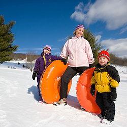 A woman and her two young kids (age 3 and 6) on a sledding hill in Quechee, Vermont.