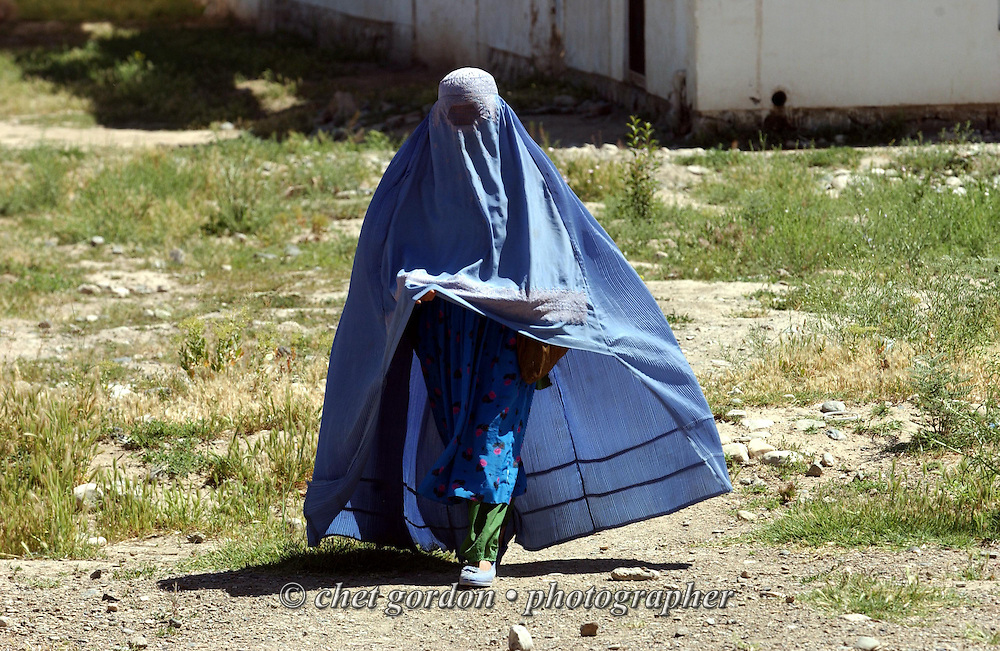 """An Afghan woman dressed in traditional burka leaves the feeding center near the Charasyab health clinic approximately 20 kilometers outside of Kabul, Afghanistan on Sunday, May 26, 2002. The women are taught nutrition, cooking and feeding techniques in a program sponsored by the German NGO, Hammer Forum. A humanitarian mission organized by The Geshundheit Instititute, founded by Dr. Hunter """"Patch"""" Adams, Lufthansa Cargo, and DHL Worldwide Express collaborated to ship medicines, food and orthopedic supplies to the Indira Ghandi Children's Hospital, clinics and orphanages in Kabul. Hammer Forum supervised the distribution of the donated supplies from various non-profit organizations in the U.S. and The Netherlands."""