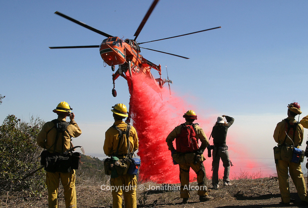 Firefighting ground crews watch as a helicopter makes a fire retardant drop on a ridge of an upper portion of Las Flores Canyon during the second day of the Malibu Canyon Fire.The fire has charred more than 2,400 acres and destroyed at least five homes and a church.The fire is about 10 percent contained today.© Copyright 2007 by Jonathan Alcorn