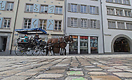 A horse drawn carriage goes through the cobble stone streets of Lucerne, Switzerland.