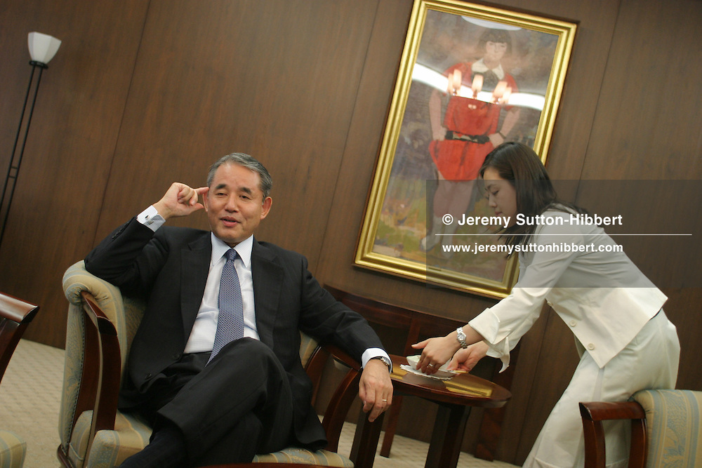 An employee positions a drink for Yasuchika Hasegawa, President and CEO of Takeda Pharmaceutical Company Limited, Tokyo, Japan, on Monday July 25th 2005.  During interviews it is common for female assistants to enter the rooms silently , bringing refreshment drinks of green tea, coffee, or orange juice, to the company head and his guests.