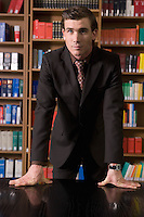 Man wearing suit leaning on desk in library portrait