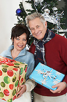 Senior couple holding presents in front of Christmas tree, portrait