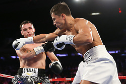 NEW YORK, NY - JULY 26: Gennady Golovkin (white trunks) throws a right hand at Daniel Geale (silver/black trunks) during their WBA/IBO Middleweight World Championship bout at Madison Square Garden on July 26, 2014 in New York, New York. (Photo by Ed Mulholland/K2 Promotions)