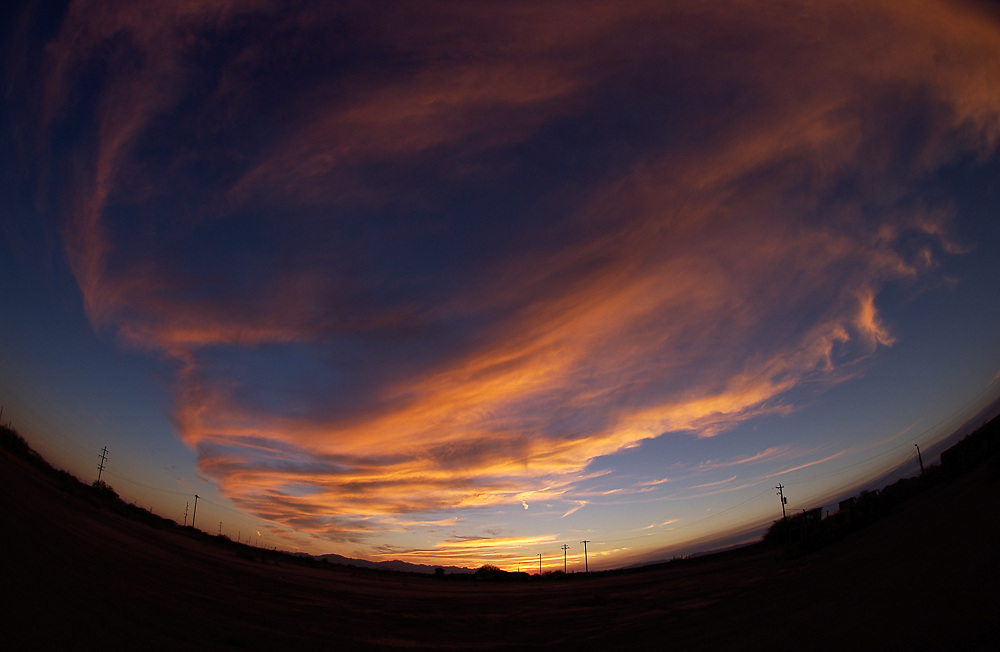orange, yellow, blue, sky, sunset, sunrise, wide-angle photography, fish-eye lens, clouds, horizon line, bending, houses, telephone lines, poles,