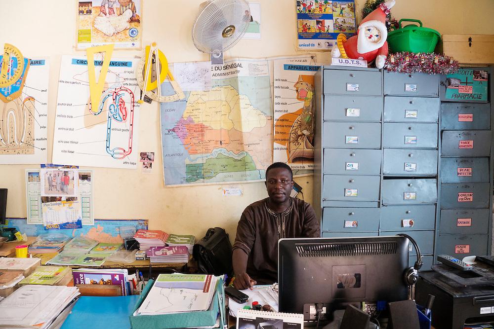 Hoofdmeester Papa Sene. De school in de wijk Guédiawaye is mede mogelijk gemaakt door de Senegalese vakbond UDTS en de Nederlandse vakbond CNV Internationaal. De wijk is in 2005 zwaar getroffen door overstromingen, waarbij veel huizen zijn verdwenen. De gevolgen hebben nog altijd een forse impact op het leven daar. Er is nog altijd geen goede irrigatie en de gezondheid lijdt onder de vervuiling.