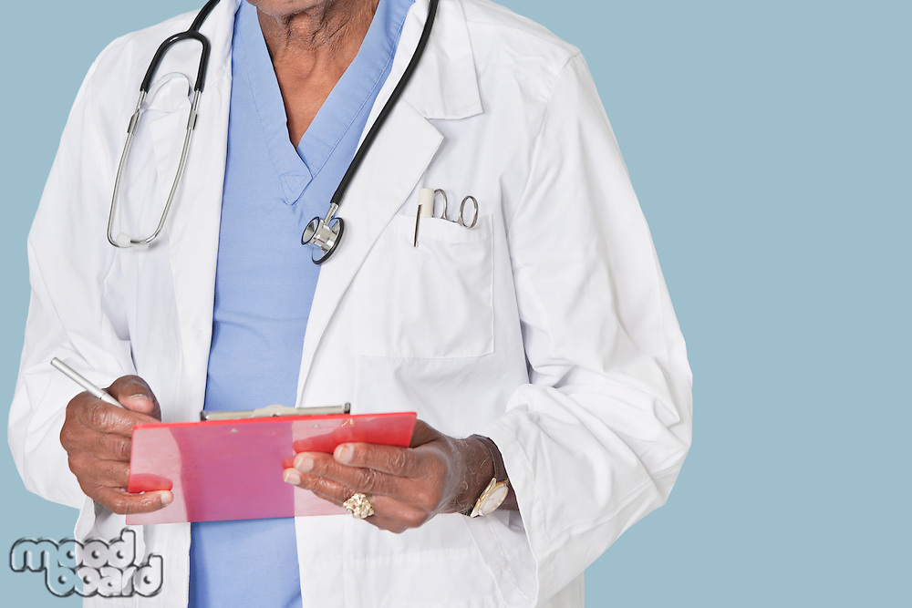 Midsection of male doctor writing on clipboard over light blue background