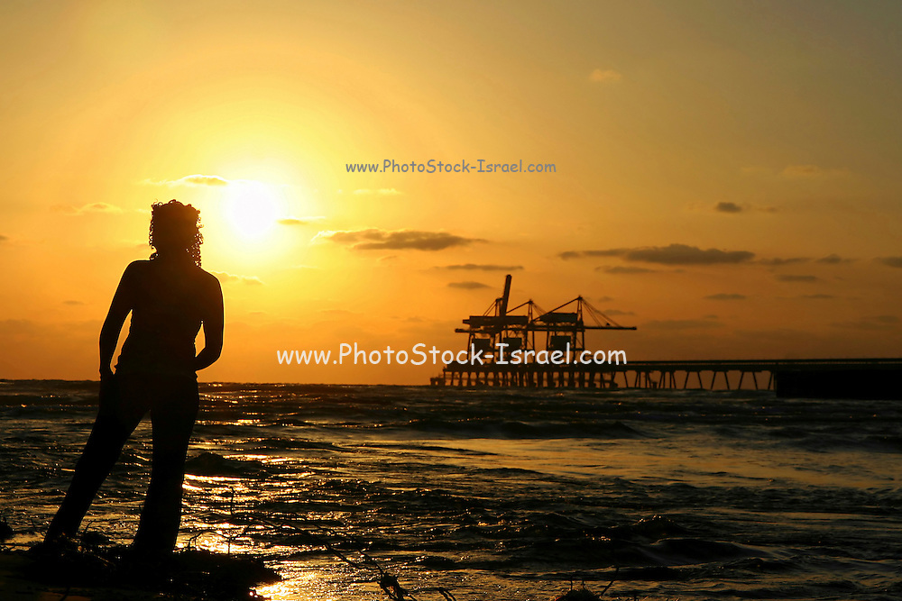 Silhouette of a woman at the beach at sunset offshore rig in the background