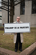 Matt Sisson, age 57, makes a statement the morning of Trump's inauguration.  Sisson said he is respectful of the day -- that&rsquo;s why he&rsquo;s wearing a suit. But he wanted to protest Trump. The sign cost $109 to have made.<br />