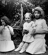 young French children play in a garden. Circa 1900