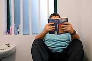 A prisoner reading in his cell. HMP Wandsworth, London, United Kingdom