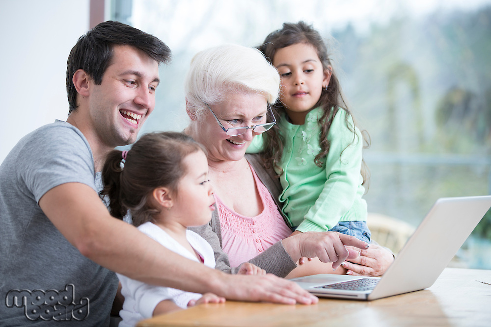 Happy three generation family using laptop at table in house