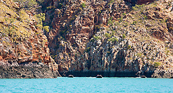 Rubber dinghies beside massive sandstone cliffs near the Horizontal Waterfalls in Talbot Bay.
