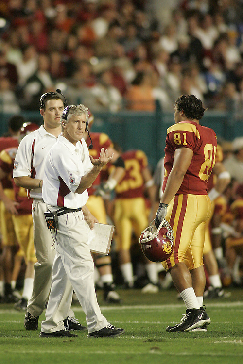 University of Southern California head coach Pete Carroll gives instructions to tight end Alex Holmes during USC's 55-19 victory over Oklahoma on January 4, 2005 in the FedEx Orange Bowl at Pro Player Stadium in Miami, Florida.