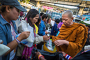 "15 JANUARY 2014 - BANGKOK, THAILAND: A Buddhist monk collects alms from protestors at the main protest site for Shutdown Bangkok. Tens of thousands of Thai anti-government protestors continued to block the streets of Bangkok Wednesday to shut down the Thai capitol. The protest, ""Shutdown Bangkok,"" is expected to last at least a week. Shutdown Bangkok is organized by People's Democratic Reform Committee (PRDC). It's a continuation of protests that started in early November. There have been shootings almost every night at different protests sites around Bangkok. The malls in Bangkok are still open but many other businesses are closed and mass transit is swamped with both protestors and people who had to use mass transit because the roads were blocked.    PHOTO BY JACK KURTZ"